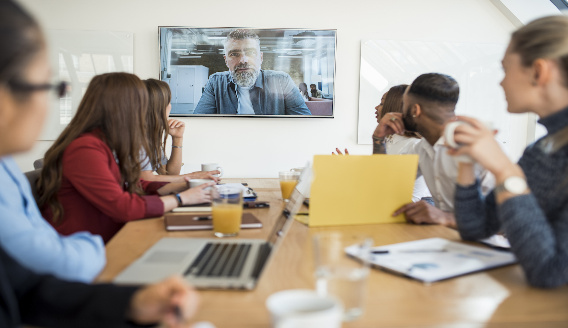 Group of businesspeople having a video conference call with their superior